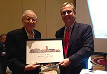 Dr. Larry Davis, UMSL Dean, right, presents Dr. Lester Caplan with a framed print of the campus.