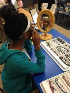 A student tries on frames received through the Illinois Eye Institute at Princeton Elementary.